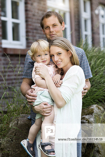 Eltern mit ihrem kleinen Sohn vor dem Haus