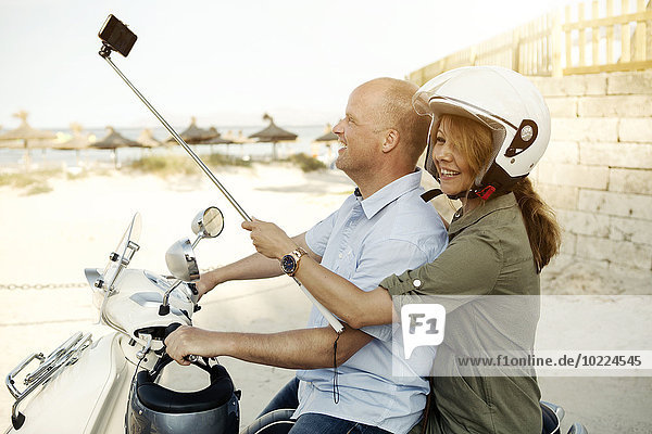 Spanien  Mallorca  Alcudia  Paar mit Selfie Stick auf Motorroller