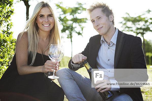 Elegantes junges Paar im Freien beim Weintrinken