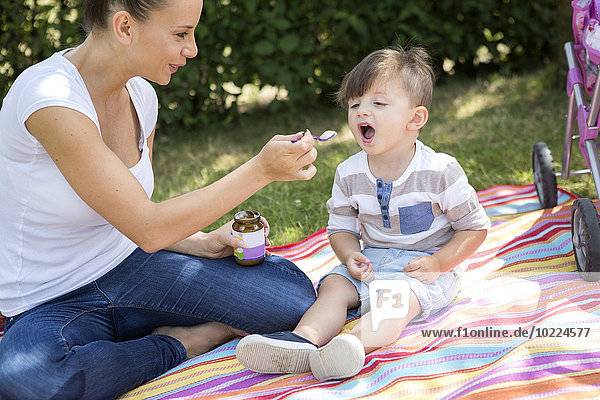 Mutter füttert ihren kleinen Sohn auf einer Decke.