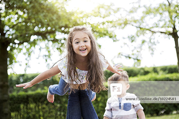 Porträt eines kleinen Mädchens  das auf dem Knie seiner Mutter balanciert.