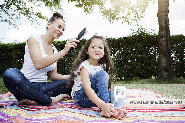 Mutter bürstet das Haar ihrer kleinen Tochter.
