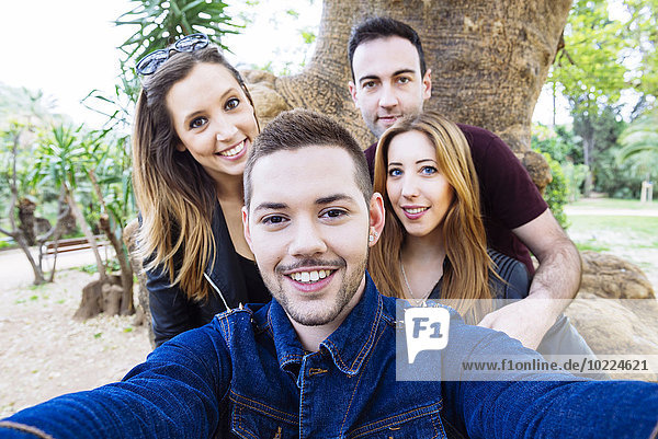 Four friends taking a selfie in a park