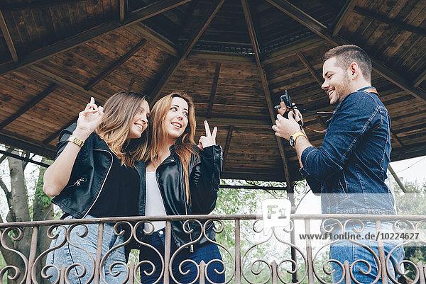 Spanien  Barcelona  junger Mann beim Fotografieren seiner beiden Freundinnen