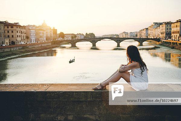 Italien  Florenz  Frau in weißem Sommerkleid bei Sonnenuntergang auf einer Brücke sitzend