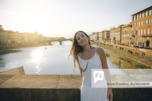 Italien  Florenz  Porträt einer Frau in weißem Sommerkleid  die bei Sonnenuntergang auf einer Brücke steht.