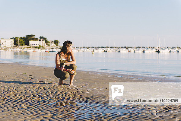 France  Pornichet  woman crouching on the beach at sunset