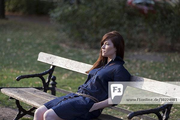 Porträt einer Frau auf einer Parkbank sitzend