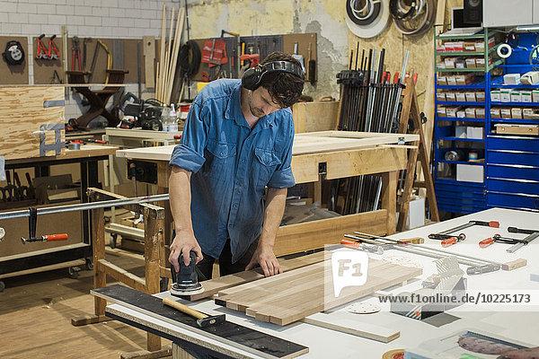 Schreiner mit Schleifmaschine in der Werkstatt