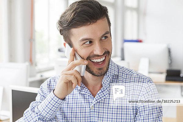 Porträt eines lächelnden Geschäftsmannes beim Telefonieren im Büro