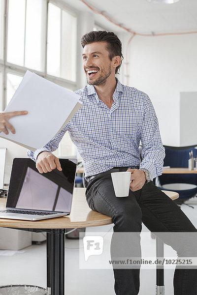 Porträt eines lächelnden Geschäftsmannes mit Kaffeetasse im Büro