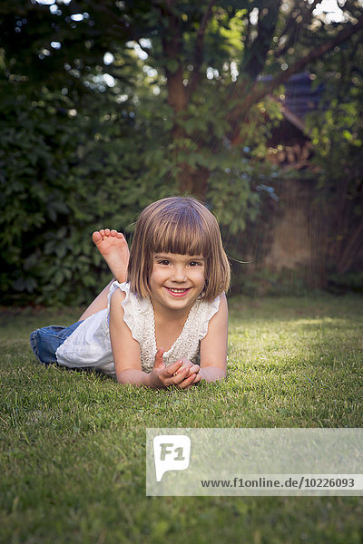 Smiling little girl lying on the meadow in the garden