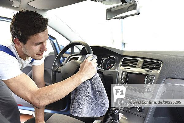 Mann reinigt Autoinnenraum