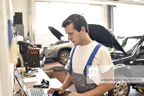 Car mechanic using laptop in a garage