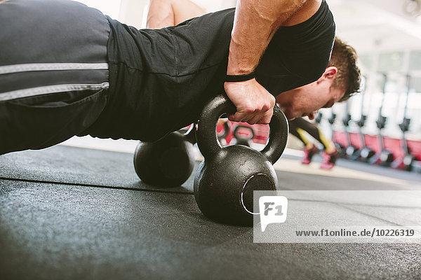 CrossFit-Athlet beim Liegestütz auf Kettlebells