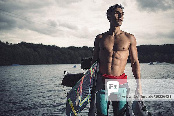 Junger Wakeboarder mit seiner Ausrüstung am Seeufer stehend