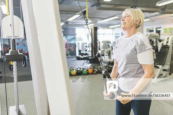 Lächelnde Seniorin in der Turnhalle beim Training an der Kabelmaschine