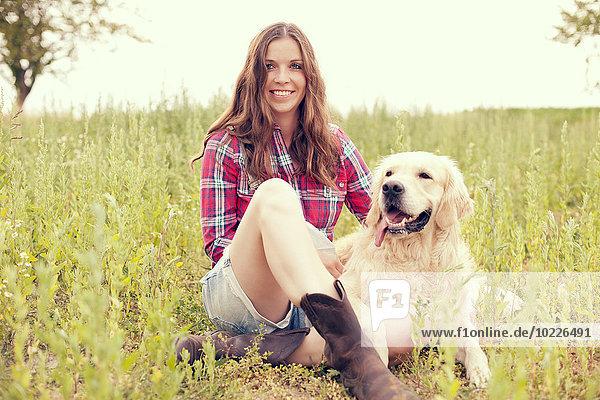 Frau und ihr Golden Retriever auf einer Wiese sitzend