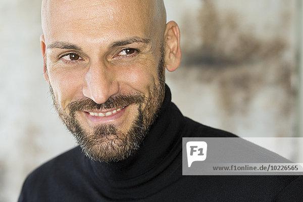 Porträt eines lächelnden Mannes mit schwarzem Rollkragenpulli