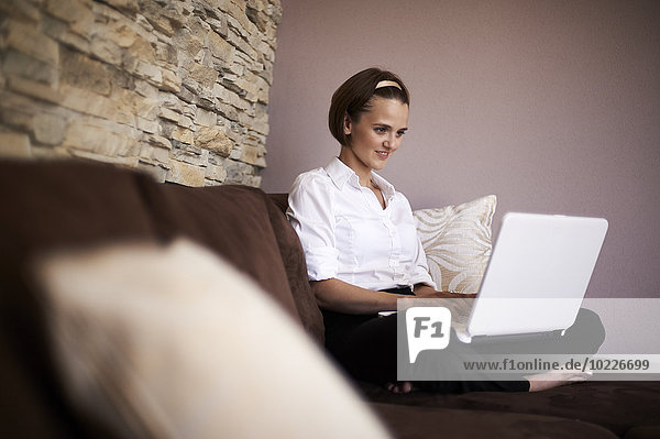 Woman sitting cross-legged on couch using laptop