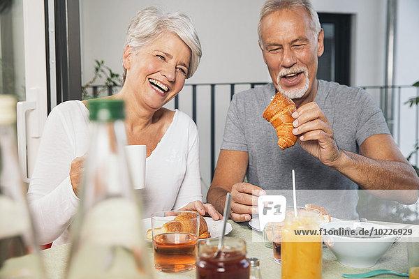 Älteres Paar beim Frühstück auf dem Balkon