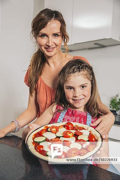 Mutter und Tochter präsentieren hausgemachte Pizza