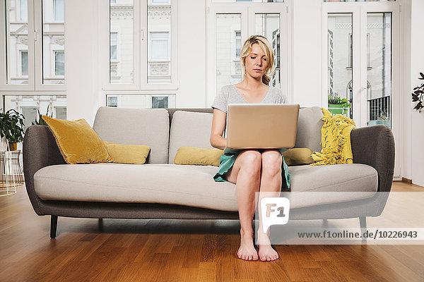 Frau sitzend auf einer Couch im Wohnzimmer mit Laptop