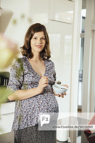Porträt einer schwangeren Frau mit Müslischale in der Küche