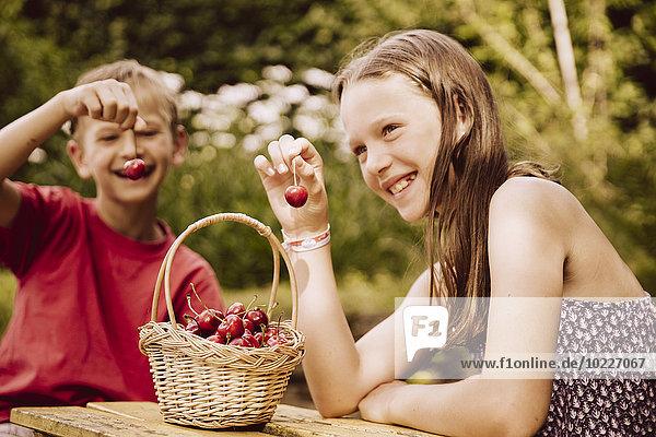 Girl and boy enjoying cherries in garden