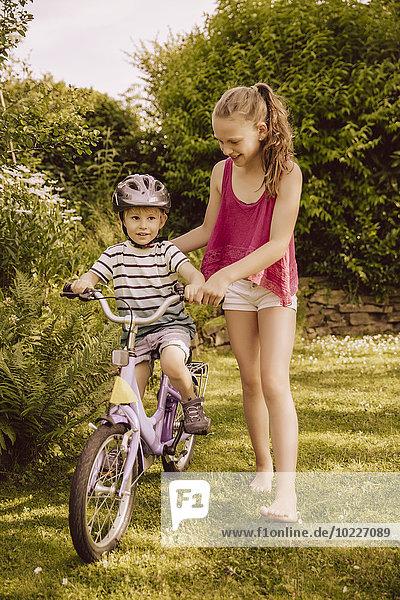 Mädchen hilft dem kleinen Jungen beim Fahrradfahren im Garten