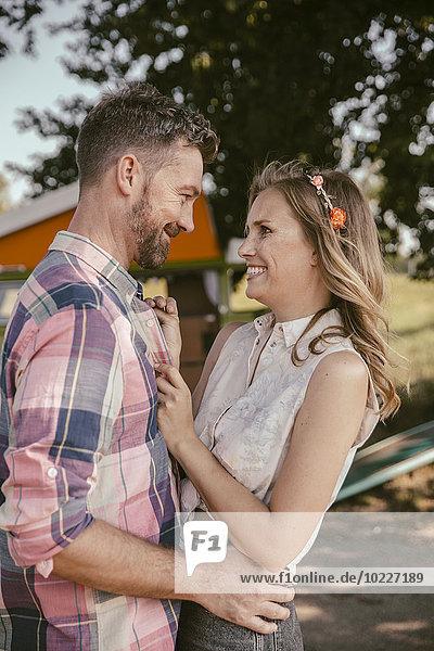 Ein glückliches Paar lächelt sich an.
