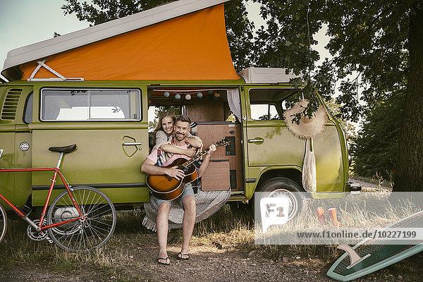 Lächelnde Frau umarmt den Mann im Van und spielt Gitarre.