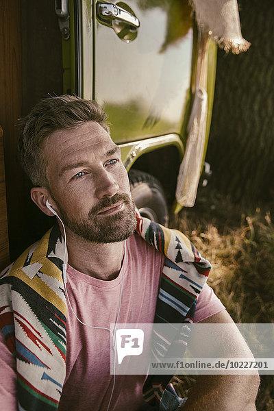 Mann hört Musik vor dem Van