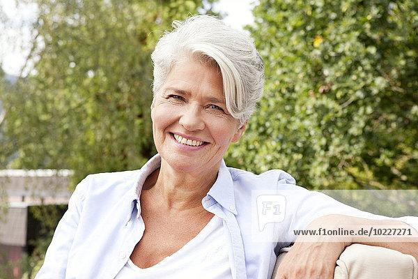 Porträt einer lächelnden reifen Frau im Freien