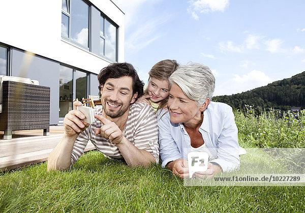 Glückliche Großmutter  Vater und Mädchen auf dem Rasen liegend mit dem Handy