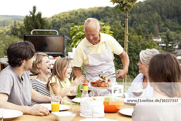 Großvater serviert das Essen vom Grill für die Familie am Gartentisch.