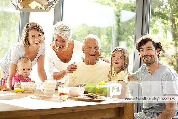 Porträt der glücklichen Großfamilie mit Geschenk am Frühstückstisch