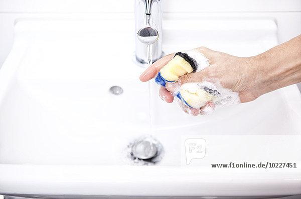 Frau Reinigung Bad Waschbecken mit Schwamm