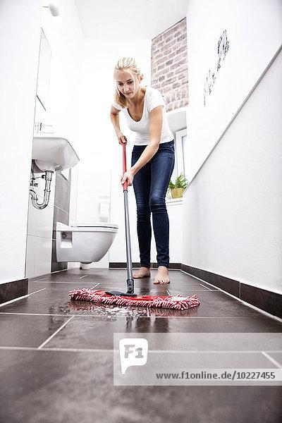 Frau wischt den Boden im Bad ab