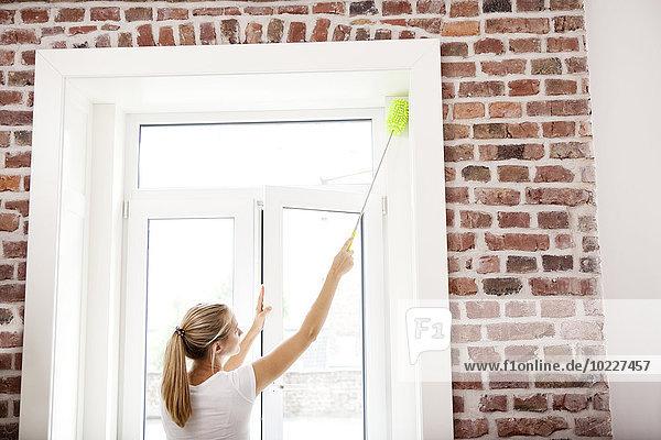 Frau  die das Fenster abstaubt