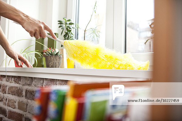 Frau reinigt Fensterbank mit Staubwedel