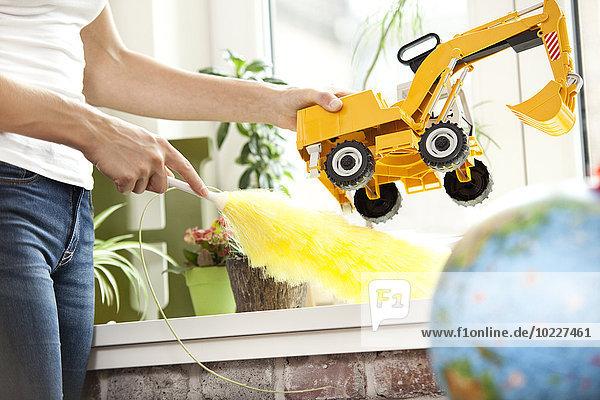 Frau reinigt Fensterbank im Kinderzimmer