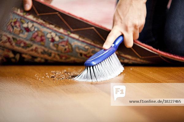 Frau fegt unter den Teppich