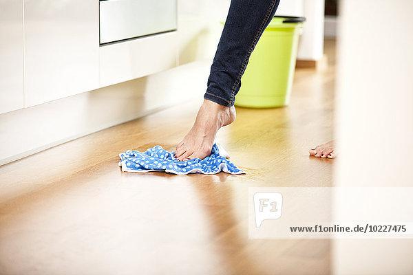Frau mit nackten Füßen wischt den Boden ab