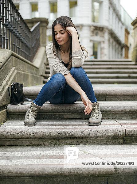 Spanien  Oviedo  junge Frau auf einer Treppe in der Altstadt sitzend