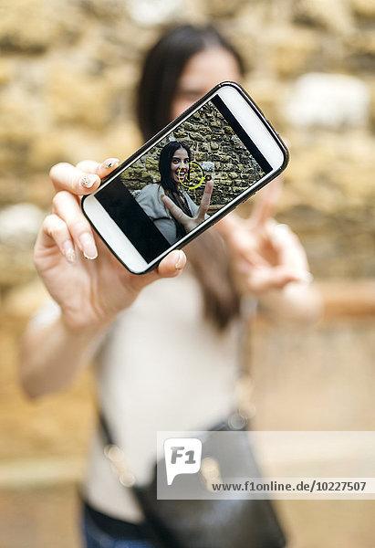 Smartphone mit Foto einer lächelnden Frau  die einen Selfie macht.