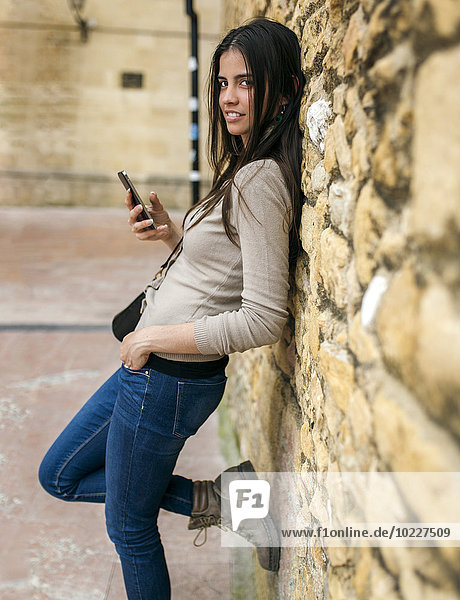 Young woman with smartphone leaning against stone wall