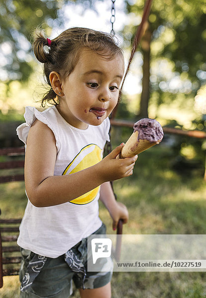 Little girl trying to eat ice cream
