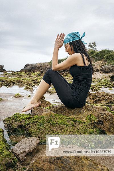 Spanien  Asturien  Gijon  Frau beim Yoga an einem Felsenstrand