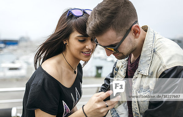 Spanien  Gijon  junges Paar beim Betrachten von Bildern auf dem Smartphone